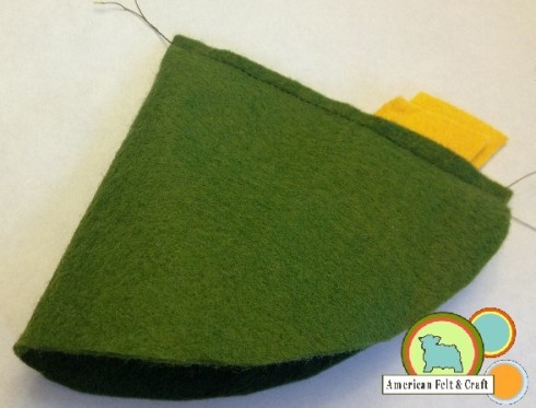 Fold over and sew down the straight edge using a running stitch and ...