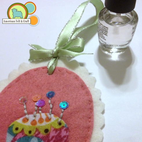 Finishing a felt ornament with ribbon - use clear nail polish to keep ribbon from fraying